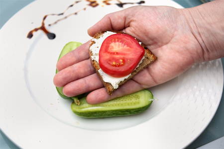 sandwich spread: Hand holding a sandwich with spread and tomato, overhead closeup shot