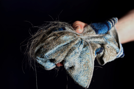 Female hand gripping a dirty cloth, studio cropped shot Imagens