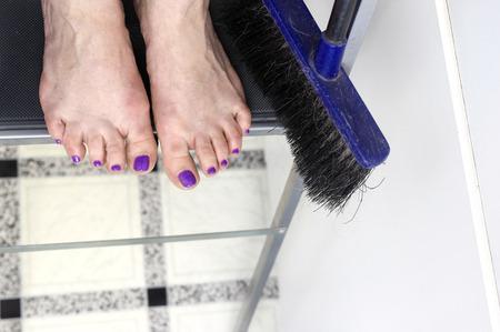 bare feet: Overhead shot of female bare feet standing on ladder next to broom