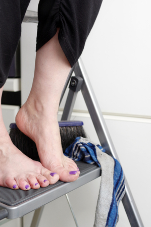 bare feet: female bare feet with pedicure standing on ladder next to short brush, vertical indoor shot with focus in foreground Stock Photo