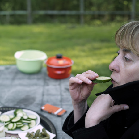 side shot: Side shot of a woman tasting cucumber, selective focus shot made in a windy summer day Stock Photo