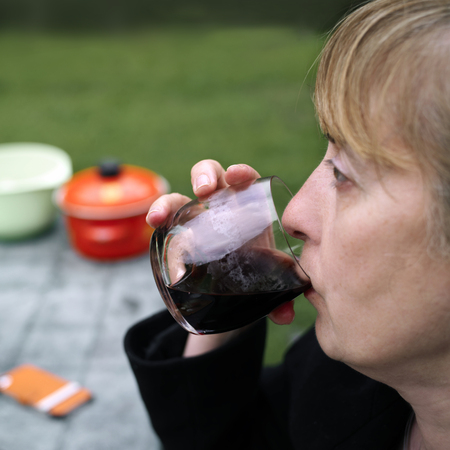side shot: Side shot of a woman tasting red wine, sitting outdoor. Focus on the wine glass, blurred background