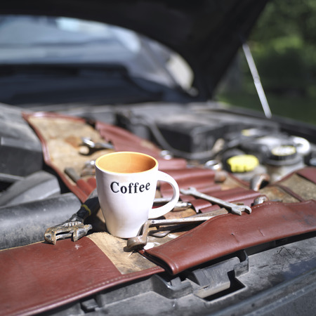 Open car hood, set of tools and coffee cup on top, fay time shot with selective focus and blurred background