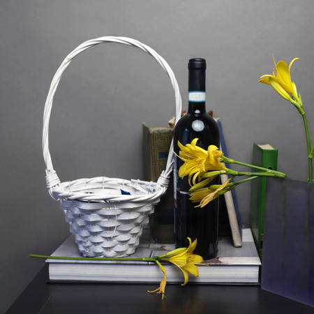 day lily: Wicker basket and a bottle of red wine next to the vase with beautiful yellow day lily, front studio shot