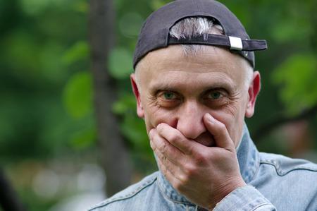 arrepentimiento: hombre t�mido que desgasta el casquillo hacia atr�s a punto de re�r, recorta el retrato al aire libre