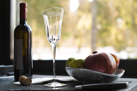 contra: Bottle of red wine and fruits laid on the table, window in the blurred background, interior contra light shot Stock Photo