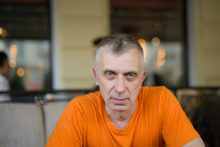 Matured man staring at camera, sitting in cafeteria or restaurant. Front cropped shot Stock Photo
