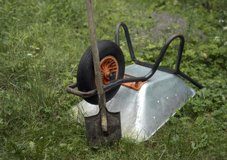 tipped: Garden trolley tipped overnext to the shovel, focus in the foreground. Concept of the end of job Stock Photo