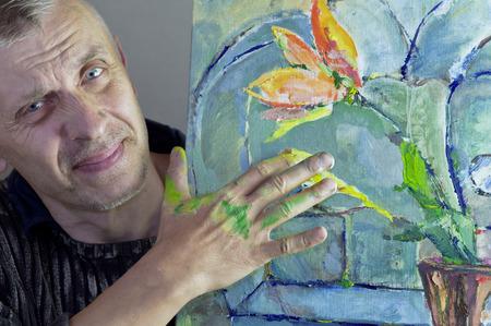 manos sucias: Un artista madurado trabajando en su pintura con las manos sucias, estudio tiro cosechado