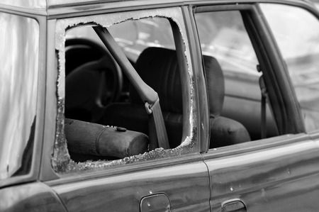 smashed: A car window smashed, particular focus on the seat belt, concept of safety on the roads. In black and white Stock Photo