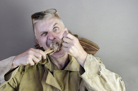 matured: A matured man wearing shabby clothes gnawing a bone, studio portrait Stock Photo
