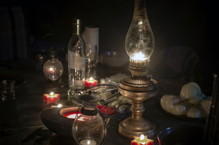 blackout: A kerosene lamp in focus and candles around the table with some food and drinks left, night scene, concept of blackout