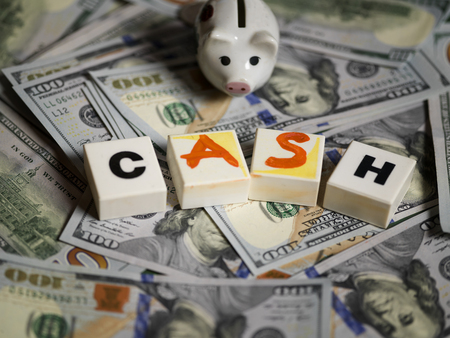 money box: Pig money box and playing cubes with written word Cash laid on the pile of US currency, studio closeup, concept of business and finance Stock Photo