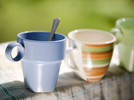 tidiness: A bunch of tea mugs standing in a row on a clean kitchen towel, selective focus closeup