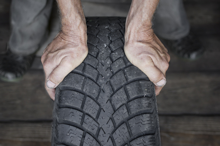 tire tread: Hands of mechanic holding a tire with a winter tread in a garage, indoor front shot with selective focus Stock Photo