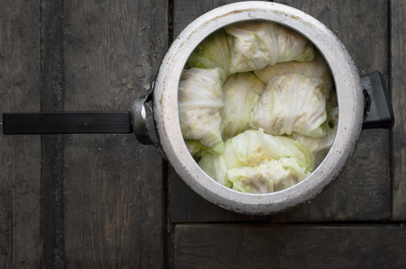 ready to cook food: A casserole with cabbage leaves and minced meat on a wooden floor or table, overhead indoor shot