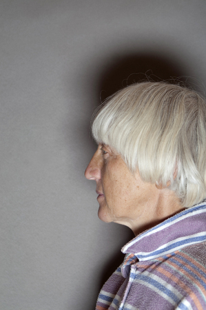 side shot: Side shot of a beautiful senior female with gray hair, studio vertical shot on gray