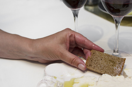 comiendo pan: Female hand with a slice of bread in focus, two glasses of red wine in the blurred background Foto de archivo