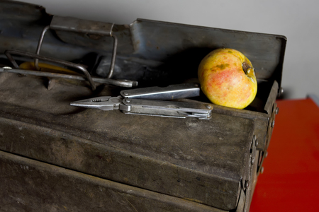angled: Pliers laid on the rusty tool box next to the ripe apple, angled studio shot Stock Photo
