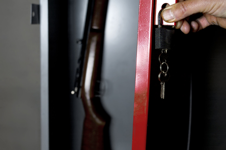 gun room: Human hand opening a metal safe with a gun inside, studio cropped shot Stock Photo