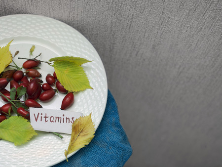 cropped shot: Bunch of red berries laid on the plate with a written word Vitamins, selective color cropped shot