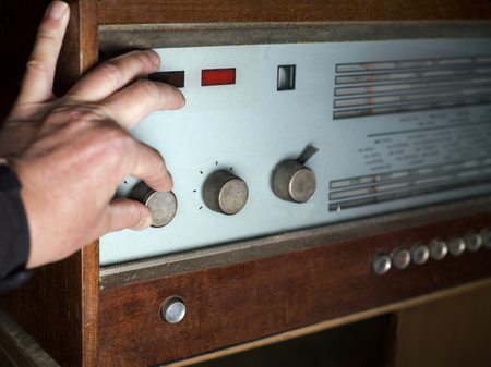 volume knob: A male hand pushing a volume knob on a looking retro receiver, shallow depth of field Stock Photo