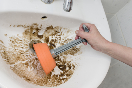 Female hand with a rubber plunger and a clogged sink full of dirt, close up shot with selective focus
