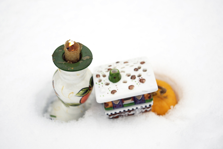 candle holder: Candle holder with burning flame and toy house on the snow