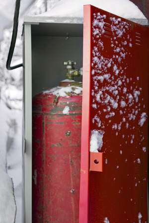 butane: Gas bottle in a safe box standing outdoor, next to the house. Snow piles in the background.