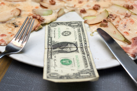 One dollar bill laid on a plate with pizza, selective focus closeup, concept of food expenses