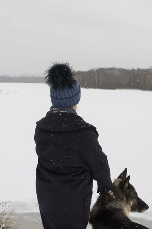 warm clothes: Woman wearing warm clothes walking with a shepherd dog, vertical outdoor shot