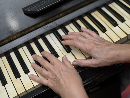 angled: Angled shot of the female hands playing on retro piano