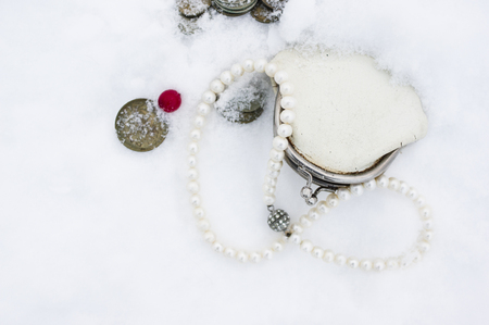 A looking retro wallet, coins and a necklace laid abandoned on the snow, overhead shot Stock Photo