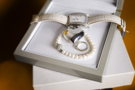 indoor shot: Ladies wrist watch, pearl necklace and a heart shape laid in the open box, closeup indoor shot