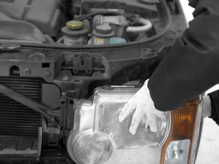 Mechanic hands in protective gloves replacing a damaged bulb or headlight, selective color shot