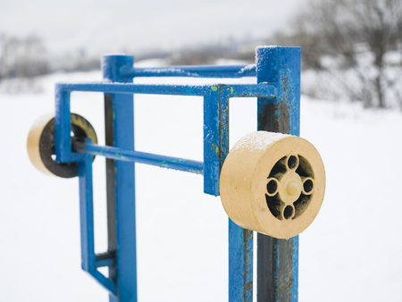 angled: A workout gym bench with a barbell covered with snow, angled outdoor shot with selective focus