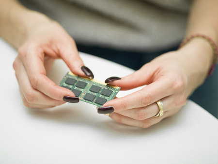 Female hands with manicure holding a memory expansion chip, shallow depth of field shot Stock Photo