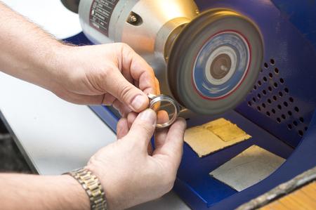 Männliche Hände, die ein Zeitstück Körper auf einer speziellen Poliermaschine, Nahaufnahme selektiven Fokus Schuss Standard-Bild