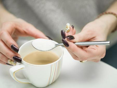 Mano manicured mujer a punto de poner azúcar en una taza de café. Profundidad de campo macro disparo