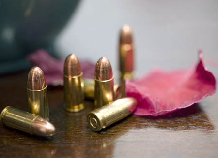 Bunch of 9 mm cartridges and a red leaf laid on a wooden table, shallow depth of field closeup