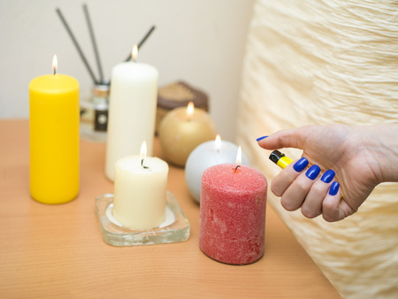 encendedores: Female hand with a lighter next to the aromatic candles, closeup indoor shot Foto de archivo
