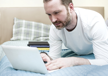 Mid adult man wearing beard typing on a laptop laid on the unmade bed, indoors cropped shot Stock Photo