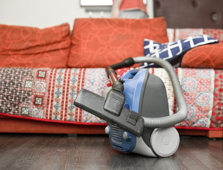 Vacuum cleaner in front of red sofa with blanket and pillows, indoor cropped shot