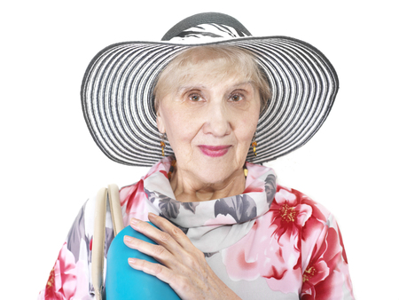 75s: Senior female wearing beautiful hat with a travel or shopping bag on a shoulder, studio shot on white