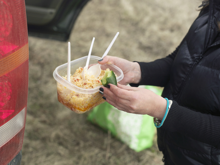 Female hands holding a plastic food container with rice, eaten cucumber. Car stop light in the foreground Imagens