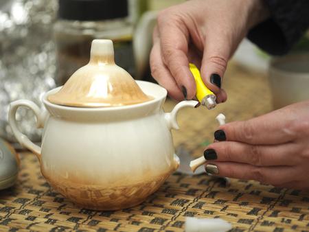 accidental: Manicured female hands gluing a broken sugar bowl, macro shot Stock Photo