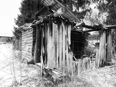 mess: Abandoned wooden house after fire, outdoor cropped shot in black and white