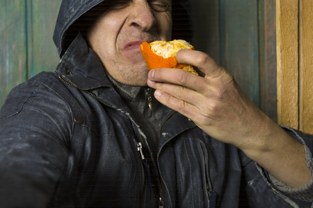 Hooded man tasting a disgusting fruit, extremely expressive cropped studio portrait