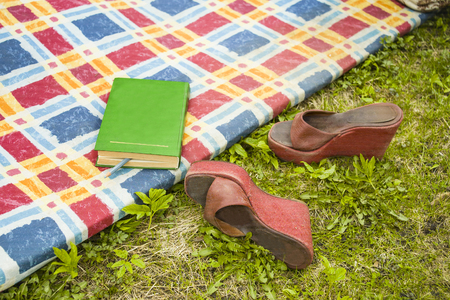 A book on a mat and high heels on the grass, outdoor cropped shot, concept of a weekend Stock Photo