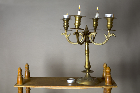 antique furniture: Burning candles in a retro bronze candle holder, placed on wooden shelf